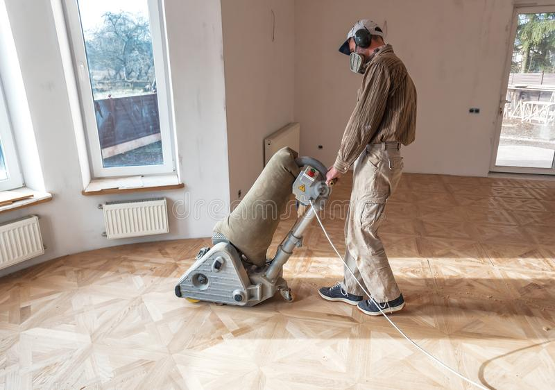 Professional master grinding a parquet with machine stock photos
