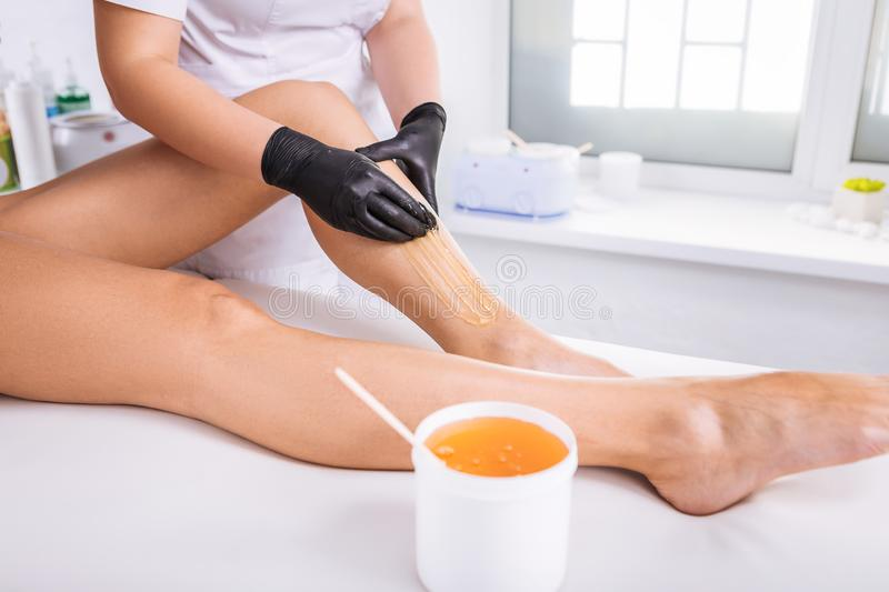 Professional master of wax depilation providing service for client royalty free stock images
