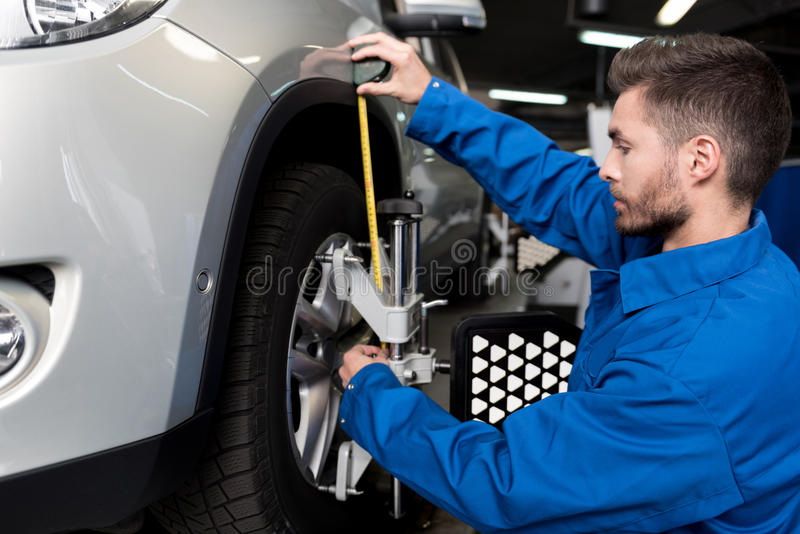 Professional mechanic adjusting automobile wheel alignment. Modern service. Pleasant young mechanic using measure tape and adjusting automobile wheel alignment royalty free stock photo