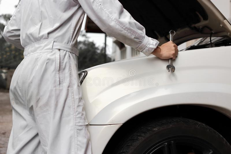 Professional mechanic man in white uniform holding wrench with car in open hood at the repair garage background. Professional mechanic man in white uniform royalty free stock images