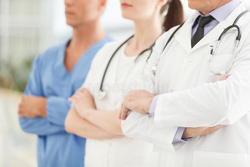 Only professional medical assistance. Cropped image of successful doctors team standing together with their arms crossed royalty free stock image