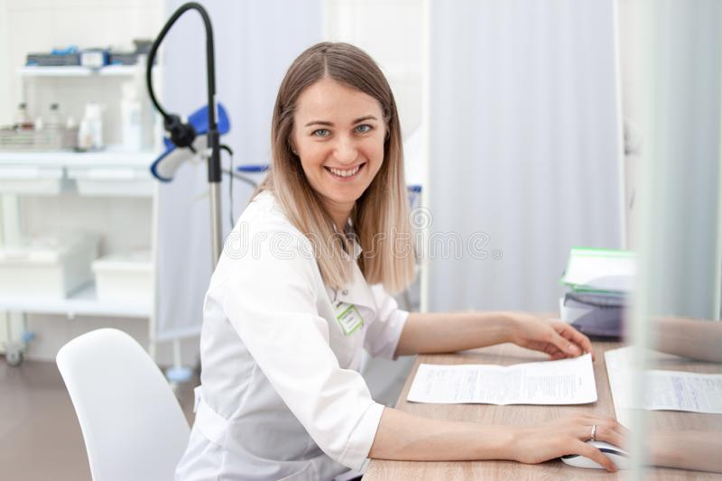 Professional medical physician gynecologist doctor in white uniform smiling at camera. Gynecological cabinet with chair stock photography