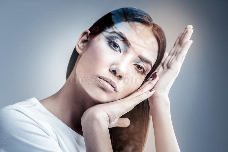 Professional model working in studio at moment. Plastic movement. Beautiful brunette raising hands and pressing lips while dreaming about rest stock photo