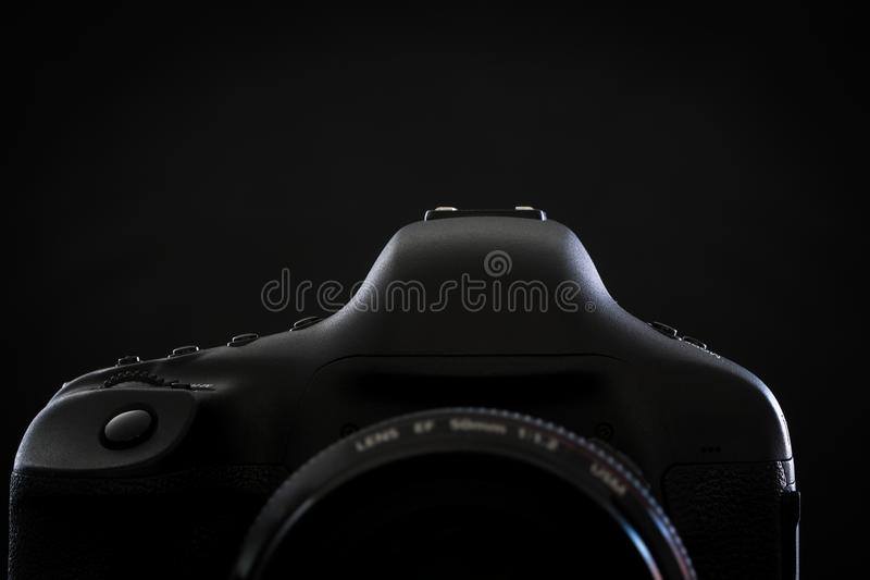 Professional modern DSLR camera low key stock photo/image. Modern DSLR camera with a very wide aperture lens on with highlighted edges against black stock photos