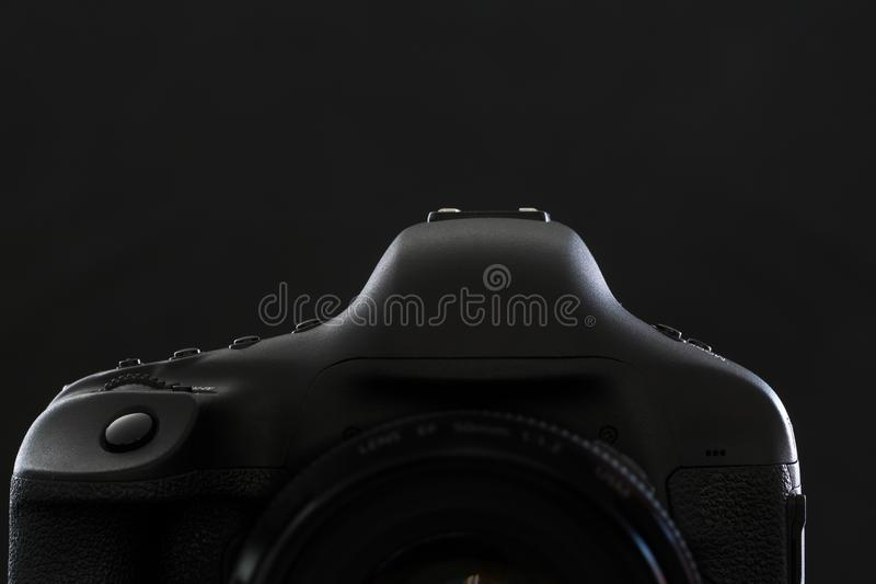 Professional modern DSLR camera low key stock photo/image. Modern DSLR camera with a very wide aperture lens on with highlighted edges against black royalty free stock photography