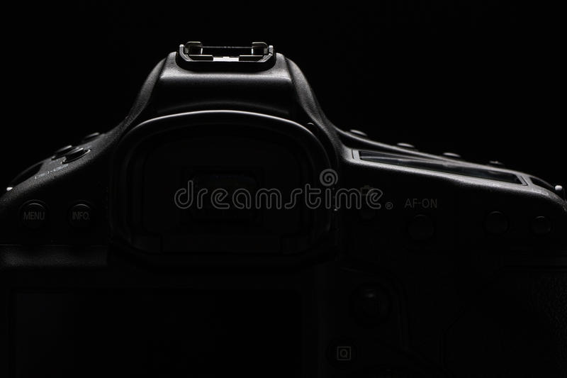 Professional modern DSLR camera low key stock photo/image. Modern DSLR camera with a very wide aperture lens on with highlighted edges against black royalty free stock photo