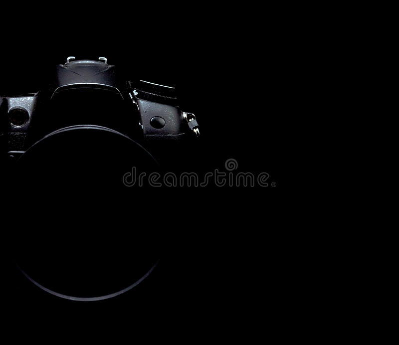 Professional modern DSLR camera low key stock photo/image. Modern DSLR camera with a very wide aperture lens on with highlighted edges against low key black stock photography