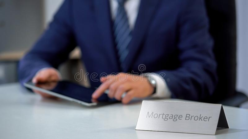 Professional mortgage broker using tablet pc, searching loan offers for client. Stock photo stock photo