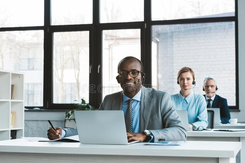 Professional multiethnic business people in headsets using laptops and smiling at camera. In office royalty free stock images
