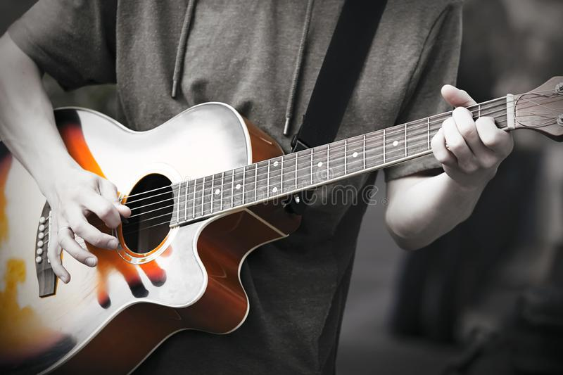 A professional musician plays an improvised melody on a six-string acoustic guitar royalty free stock photography
