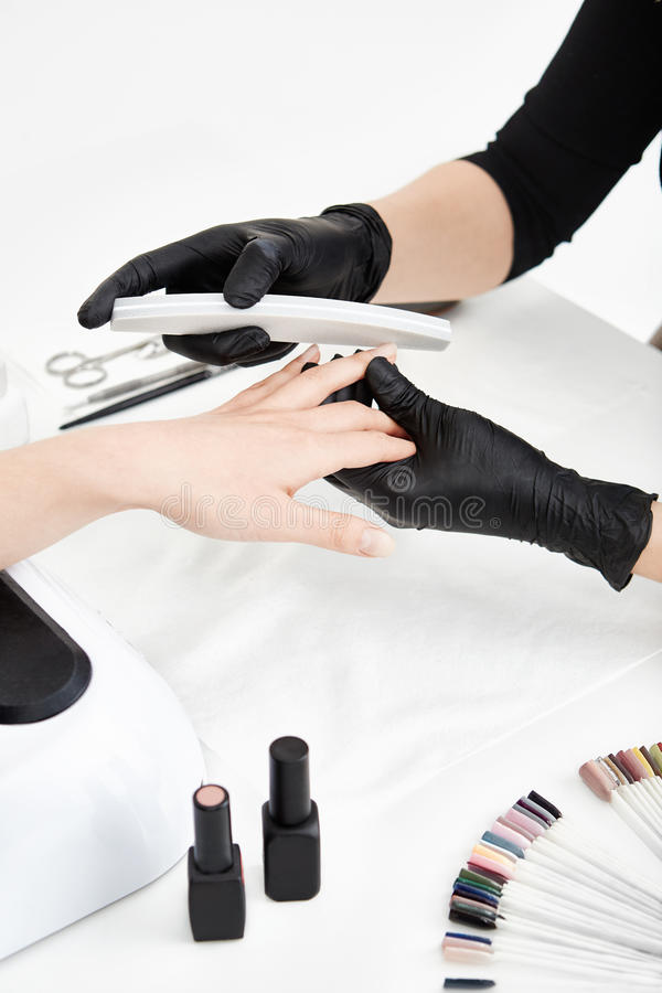 Professional nail technician filing nails before applying nail polish. Professional nail technician in black gloves shortening nails before applying nail polish royalty free stock photo