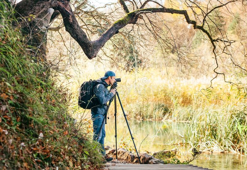 Professional Nature photographer using a tripod takes a shot of. The autumn lakes in Plitvice Lakes National Park, Croatia stock photo