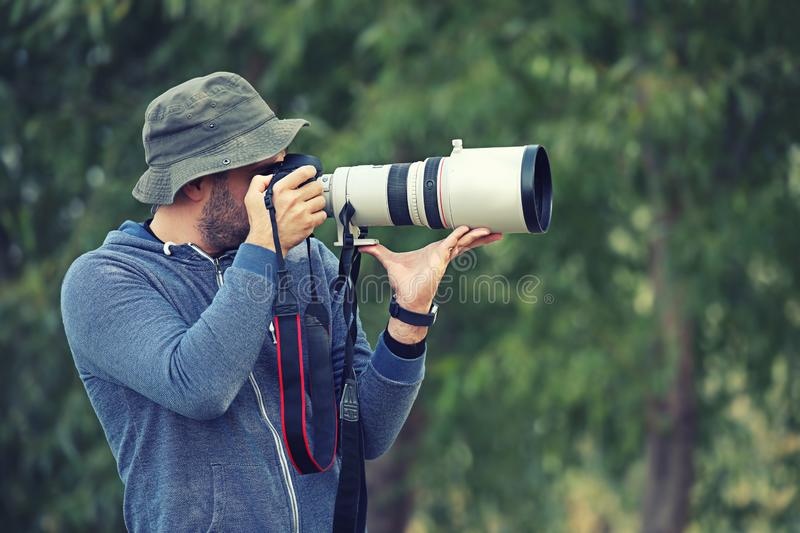 Professional nature and wildlife photographer outdoor hand holding camera with big pro lens taking pictures stock photos