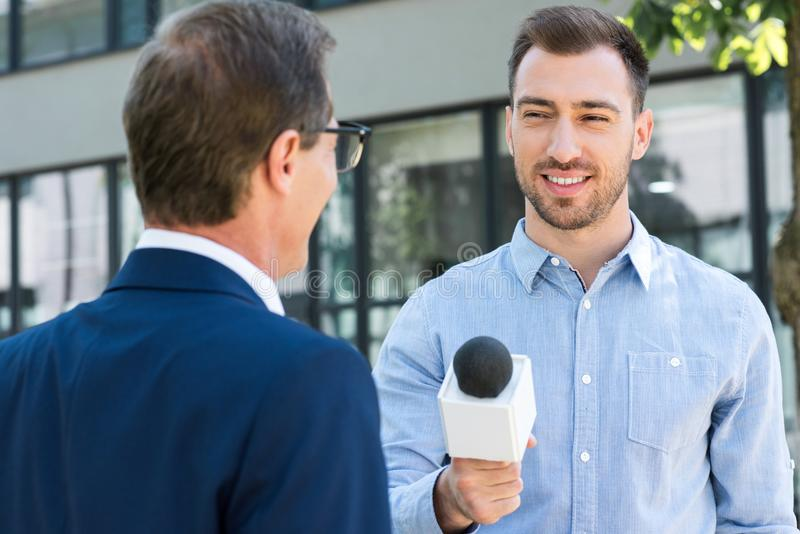 professional news reporter interviewing successful businessman stock images