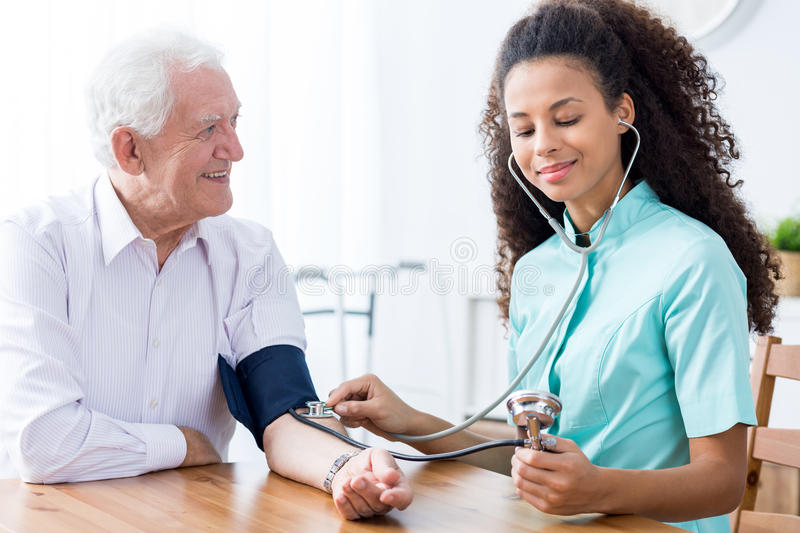 Professional nurse checking patient's blood pressure. Young happy professional nurse checking senior man's blood pressure stock photography
