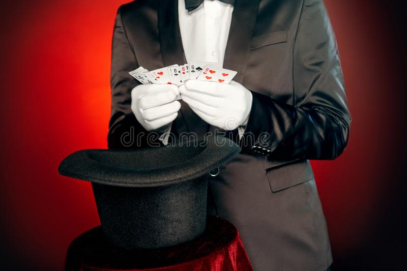 Professional Occupation. Magician in suit and gloves standing isolated on wall showing trick with cards and hat close-up royalty free stock photos