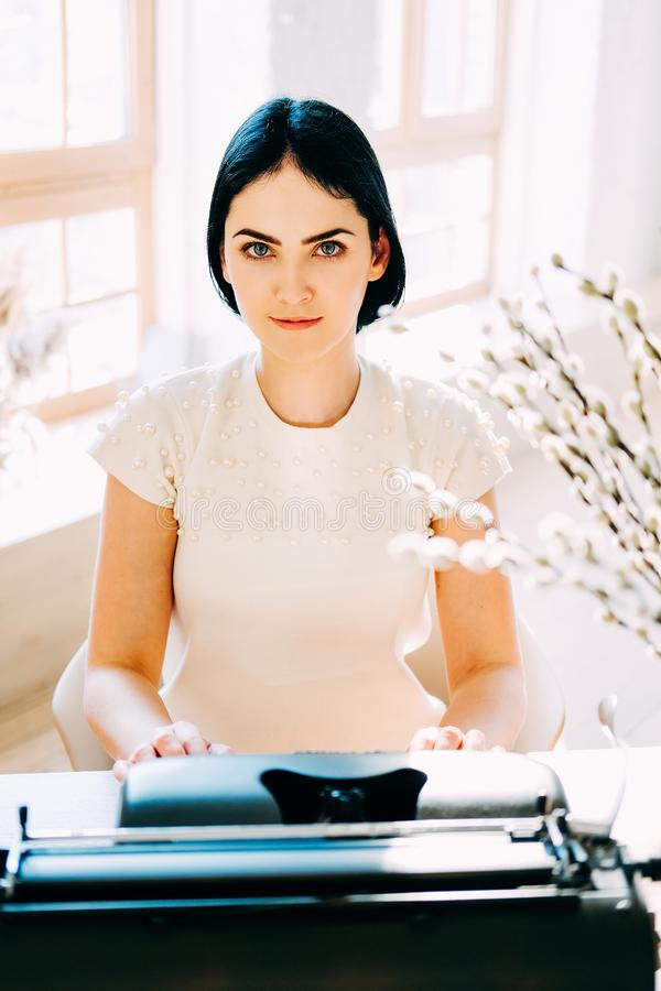 Professional occupation. Secretary in white dress typing documents stock images
