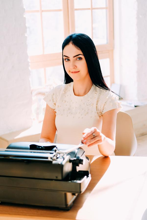 Professional occupation. Secretary in white dress typing documents royalty free stock photo
