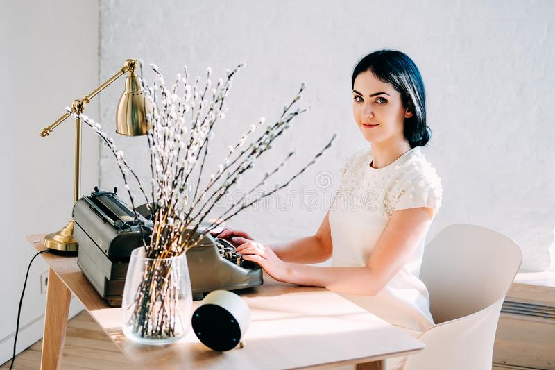 Professional occupation. Secretary in white dress typing documents stock photography