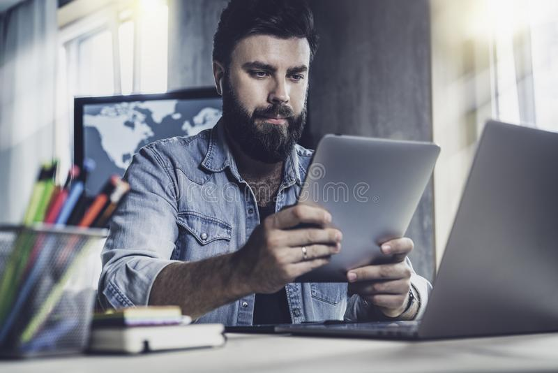 Professional at office desk using tablet in his work.Dark-haired man sitting at window in front of laptop with tablet in his hands stock images