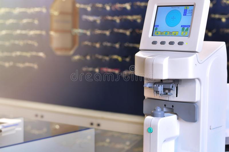 Professional ophthalmology medical instrument in clinic office and optics with glasses in background stock photography