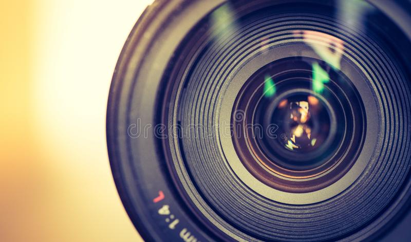 Professional optic photo lens outdoors. Warm colors, blurry background. Close up picture of a professional optic photo lens. Smooth blurry background, warm royalty free stock images
