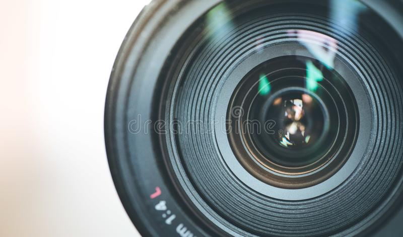 Professional optic photo lens outdoors. Warm colors, blurry background. Close up picture of a professional optic photo lens. Smooth blurry background, warm stock photo