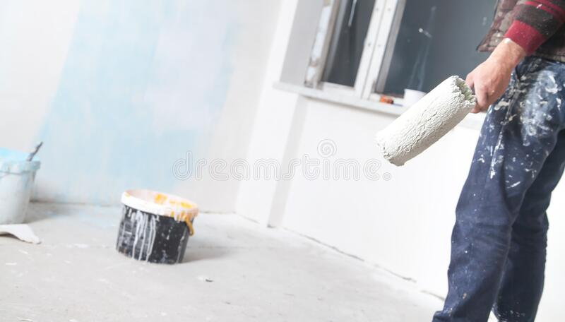 Professional painter with roller. Renovation stock images