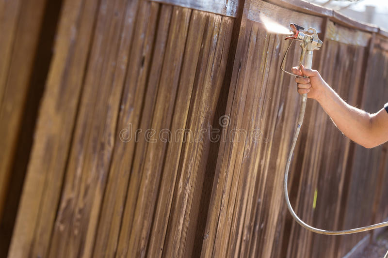 Professional Painter Spraying Yard Fence with Stain. Professional Painter Spraying House Yard Fence with Wood Stain royalty free stock image