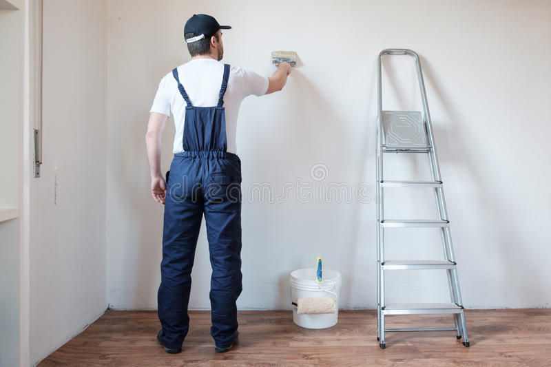 Professional painter worker is painting one wall stock image
