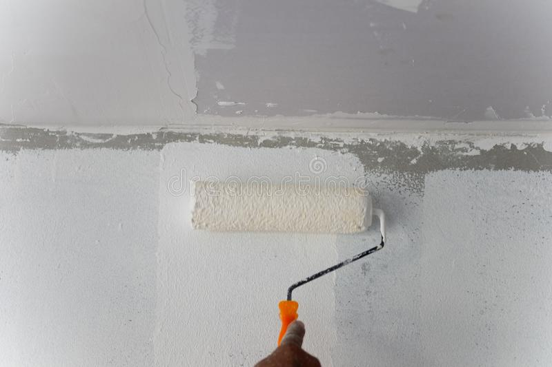 Professional painter worker is painting a wall royalty free stock photography