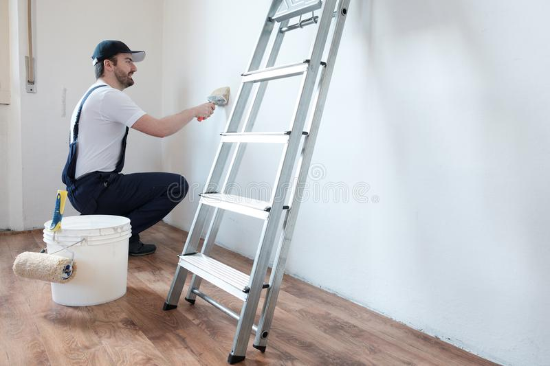 Professional painter worker is painting one wall. Professional painter worker is painting a wall stock photography