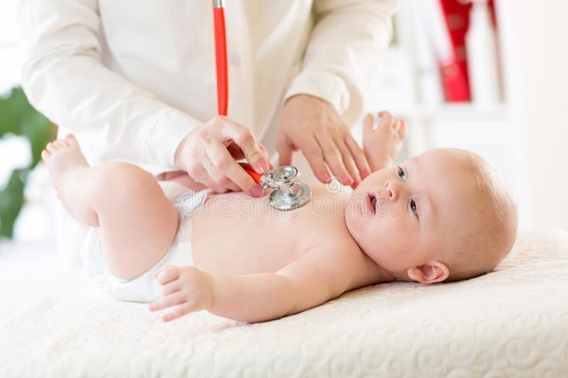 Professional pediatrician examining infant baby stock images