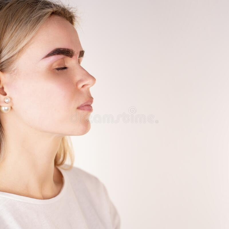 Professional permanent makeup applying on eyebrows. Close-up woman`s face with Eyebrow tattoo on a white background.  stock images