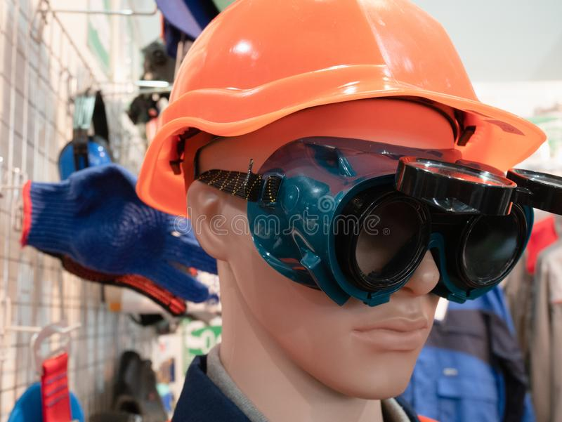 Professional personal protective safety engineering equipment for workers - dummy in orange helmet and plastic glasses royalty free stock photos