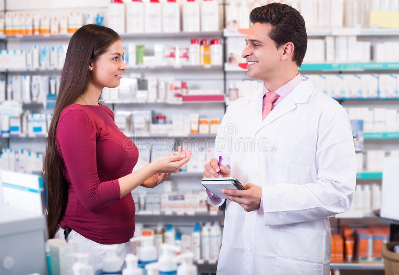 Professional pharmaceutist in drugstore helping girl. Professional russian pharmaceutist in drugstore helping girl to choose medication royalty free stock photos