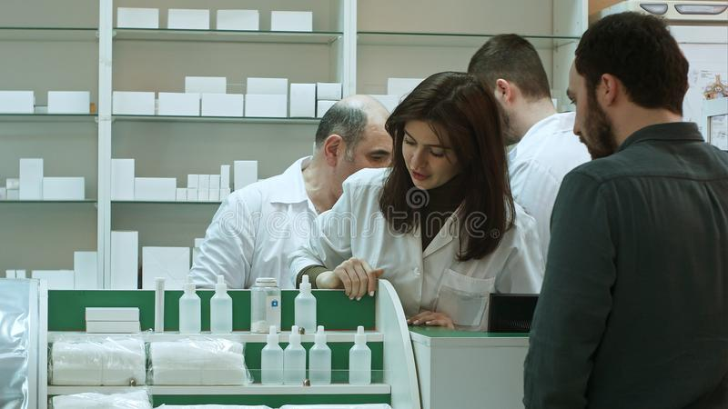 Professional pharmacist and pharmacy technician working in drugstore stock photography