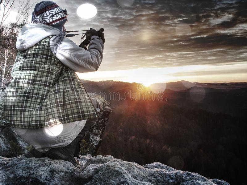 Professional photo artist stay with tripod on cliff and think stock photo
