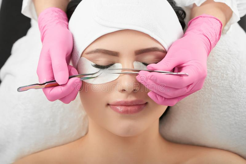 Professional photo of lashmaking in beaty salon. Photo of lashmaking in modern beaty salon. Professional is making long lashes for a client wearing pink royalty free stock image