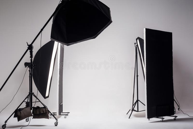 Professional photo studio with light setup included octagon softbox on boom, strip soft box and reflector on light gray background. Indoor studio shot stock images