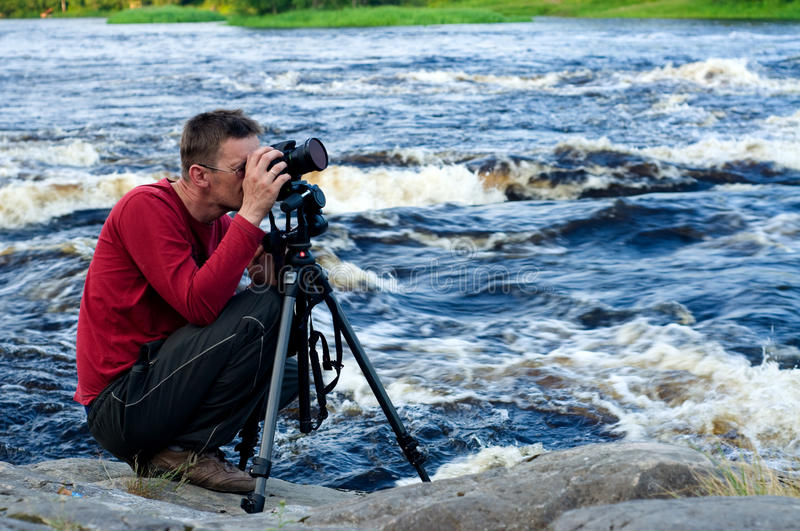 Professional photographer. Working on river bank stock image