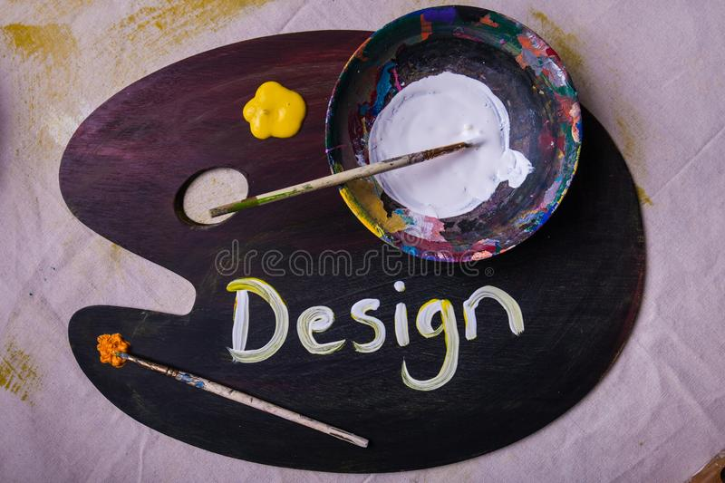Design painted on wooden artist paint mixing palette wet paint in bowl paintbrushes royalty free stock photography