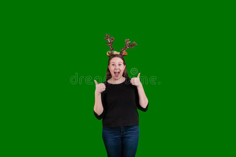 Blond female wearing Christmas reindeer antlers two thumbs up on green screen backdrop. Blond youthful female wearing Christmas reindeer antlers gesturing two royalty free stock photo