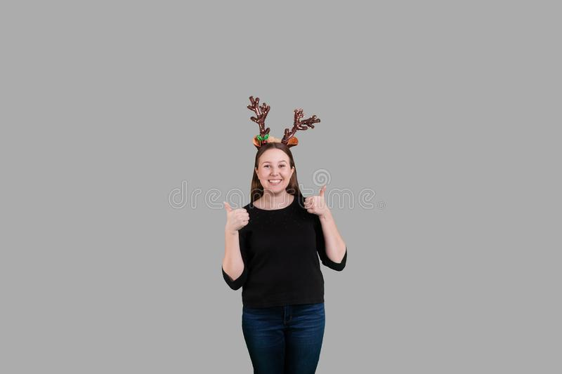 Young blonde female giving two thumbs up wearing Christmas reindeer antlers. Young blonde female giving two thumbs up wearing Christmas themed reindeer antlers royalty free stock photography