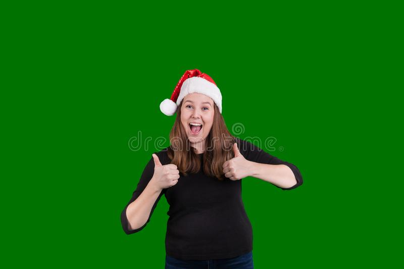 Two thumbs up hand gesture given by young blond female wearing Christmas hat. Two thumbs up hand gesture given by young blond female wearing a red and white royalty free stock images