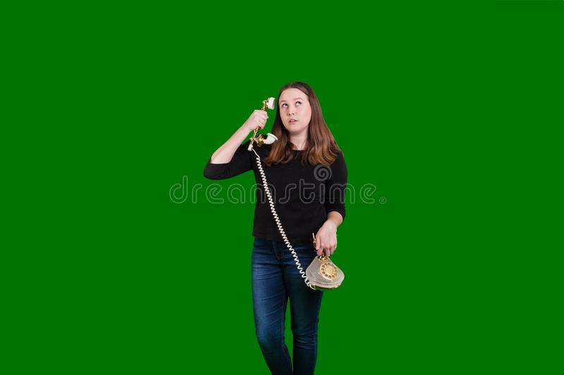 Old vintage corded telephone held by young women phone receiver held to her ear stock photo
