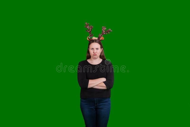 Blonde female pouting wearing Christmas themed reindeer antlers. Young blonde female pouting arms crossed wearing Christmas themed reindeer antlers captured on royalty free stock photography