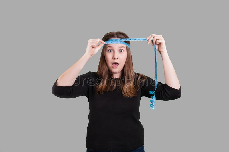 Lady measuring head with blue measuring tape surprised look on her face stock photos
