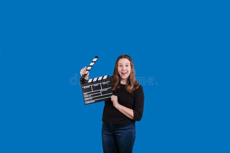 Clapperboard being used by female excited expression on solid blue background royalty free stock photos