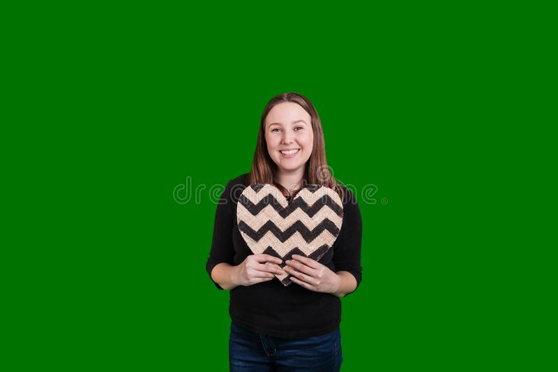 Female holding heart with white and black chevron pattern. Young female holding heart shaped sign with white and black chevron pattern smiling captured on green royalty free stock photo